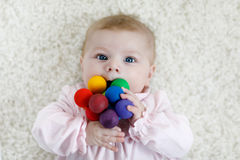 Cute baby girl playing with colorful wooden rattle toy. Cute adorable newborn baby playing with colorful wooden rattle toy ball on white background. New born Stock Photos