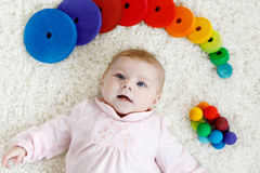 Cute baby girl playing with colorful wooden rattle toy Royalty Free Stock Photos