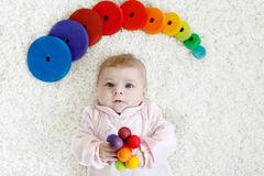 Cute baby girl playing with colorful wooden rattle toy Royalty Free Stock Photo