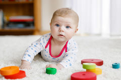 Cute baby girl playing with colorful wooden rattle toy Royalty Free Stock Photography