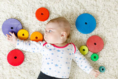 Cute baby girl playing with colorful wooden rattle toy Stock Images