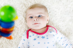 Cute baby girl playing with colorful wooden rattle toy Royalty Free Stock Images