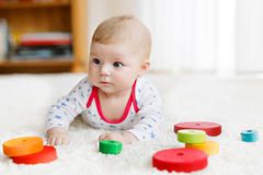 Cute baby girl playing with colorful wooden rattle toy Stock Photo
