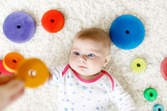 Cute baby girl playing with colorful wooden rattle toy Stock Photos