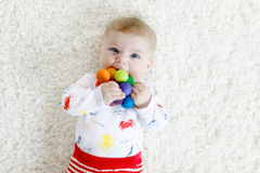 Cute baby girl playing with colorful wooden rattle toy. Cute adorable newborn baby playing with colorful wooden rattle toy ball on white background. New born Stock Image