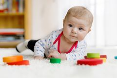 Cute baby girl playing with colorful wooden rattle toy Royalty Free Stock Image