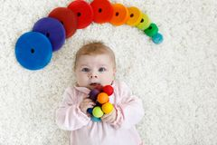 Cute baby girl playing with colorful wooden rattle toy. Cute adorable newborn baby playing with colorful wooden rattle toy ball on white background. New born Stock Photo