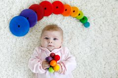 Cute baby girl playing with colorful wooden rattle toy. Cute adorable newborn baby playing with colorful wooden rattle toy ball on white background. New born Royalty Free Stock Photos