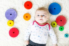 Cute baby girl playing with colorful wooden rattle toy. Cute adorable newborn baby playing with colorful wooden rattle toy ball on white background. New born royalty free stock photo