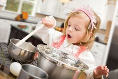 Cute Baby Girl Playing Cook With Pots and Pans In Kitchen royalty free stock photo