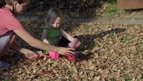 Cute baby girl playing with leaves in autumn stock video footage