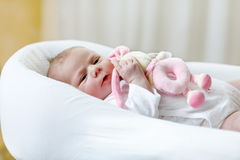 Cute baby girl playing with plush animal toy Stock Photos