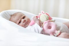 Cute baby girl playing with plush animal toy. Cute adorable newborn baby playing with pink plush animal rattle toy. in white bed at home. New born child, little Royalty Free Stock Photo