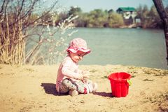 Cute baby girl playing in the sand with a red bucket stock photo