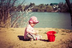Cute baby girl playing in the sand with a red bucket stock photography