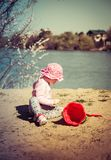 Cute baby girl playing in the sand with a red bucket royalty free stock image