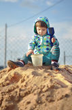 Cute baby girl playing with sand in a sandbox Stock Images