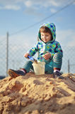 Cute baby girl playing with sand in a sandbox Royalty Free Stock Image