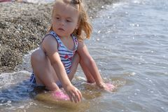 Cute baby girl is playing on sea cost with pebble, slow motion video. Cute baby girl is playing on sea cost with pebble royalty free stock photos