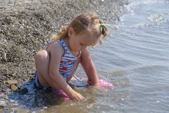Cute baby girl is playing on sea cost with pebble, slow motion video. Cute baby girl is playing on sea cost with pebble royalty free stock photo