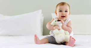 Cute baby girl playing with soft toy on bed stock video footage