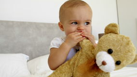 Cute baby girl playing with teddy bear on bed stock video footage