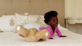 Cute baby girl playing with teddy bear on bed stock footage