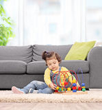 Cute baby girl playing with toy at home Stock Photos