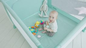 Cute baby girl playing toys in playpen at home. Top view of cheerful toddler child sitting in playpen among toys enjoying play in children`s room in loneliness stock video