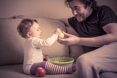 Cute baby girl plays with fruits with her father Royalty Free Stock Image
