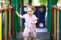 Cute baby girl plays on the playground. The one-year child runs from mother Stock Photos