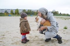 Cute baby girl plays with a puppy of a buldog outdoors. Royalty Free Stock Photos