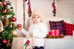Cute baby girl posing with New Year's ball in hand near Christma royalty free stock image