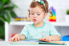 Cute baby girl reading book at home Stock Photography