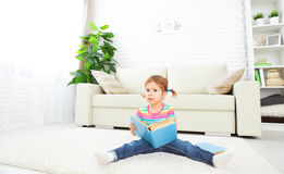 Cute baby girl reading book at home sitting on floor Stock Photo