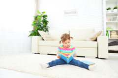 Cute baby girl reading book at home sitting on floor Royalty Free Stock Images