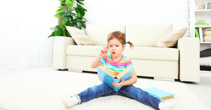 Cute baby girl reading book at home sitting on floor Royalty Free Stock Photos