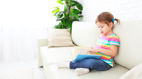 Cute baby girl reading book at home sitting on sofa Royalty Free Stock Photography