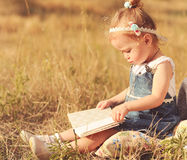 Cute baby girl reading outdoors Royalty Free Stock Photography