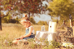 Cute baby girl reading outdoors Royalty Free Stock Photos