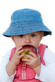 Cute baby girl with red apple. Adorable baby girl holding big red apple. Isolated on white, clipping path included, close up Stock Image