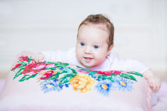 Cute baby girl relaxing on a colorful cross stitch Royalty Free Stock Photos