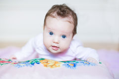 Cute baby girl relaxing on a colorful cross stitched pillow Stock Photos