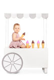 Cute baby girl seated on an ice cream stand Stock Images