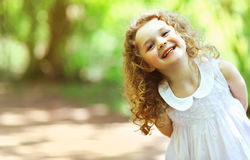 Cute baby girl shone with happiness, curly hair. Charming smile, sunny summer portrait royalty free stock photos