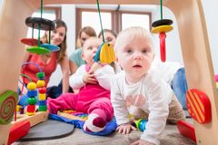 Cute baby girl showing curiosity by trying to reach multicolored toys. Cute baby girl showing progress and curiosity by trying to reach multicolored wooden toys Royalty Free Stock Images