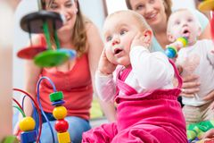 Cute baby girl showing progress and curiosity. By trying to reach multicolored wooden toys, while sitting on the floor with her mother and a family friend royalty free stock photo