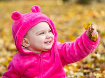 Cute baby girl sitting in autumn leaves Royalty Free Stock Photo