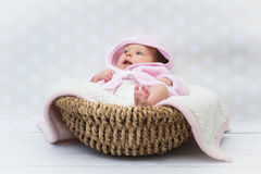 Cute baby girl sitting in a basket. Baby girl in a pink bathrobe sitting in a basket Royalty Free Stock Images