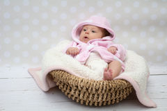 Cute baby girl sitting in a basket. Baby girl in a pink bathrobe sitting in a basket Royalty Free Stock Photo